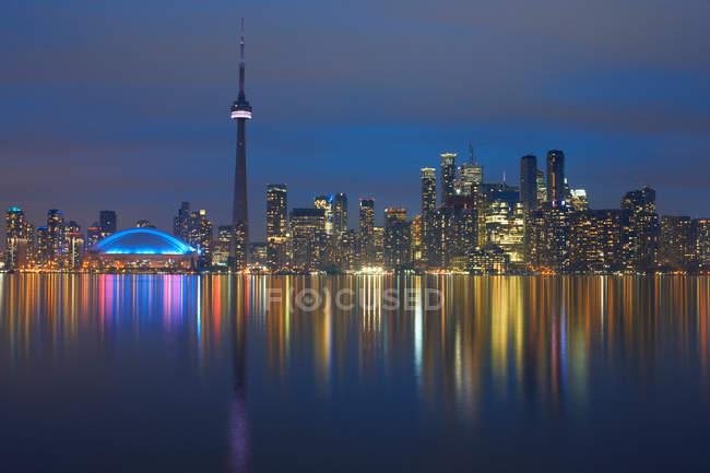 Reflection of skyline in water illuminated at night — Stock Photo