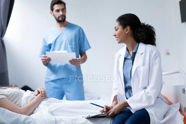 Doctors consulting with patient — Stock Photo