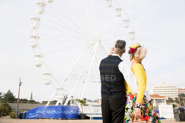 Couple pointing at ferris wheel — Stock Photo