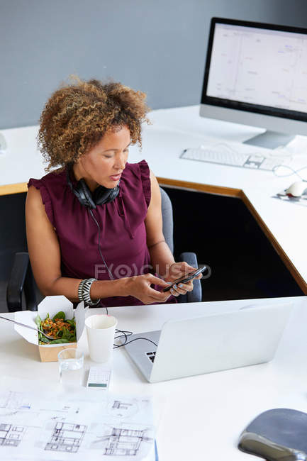 Female designer looking at smartphone — Stock Photo