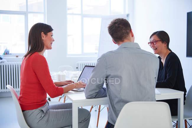 Chers collègues utilisant un ordinateur portable au bureau — Photo de stock