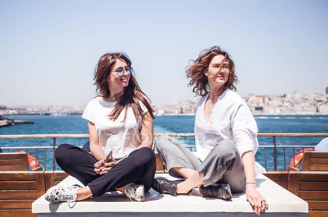 Turistas con piernas cruzadas en la cubierta del ferry de pasajeros - foto de stock