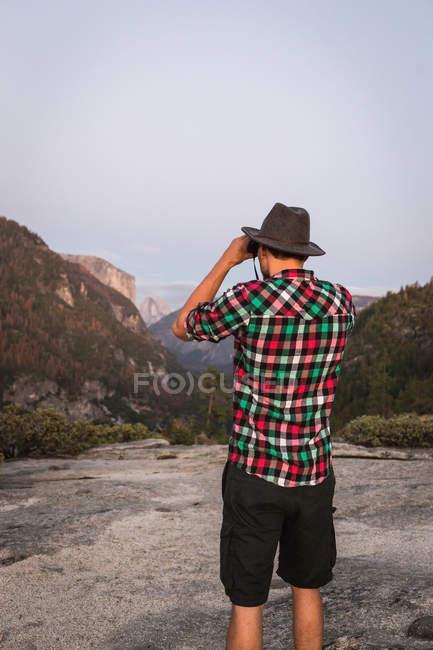 Homem olhando através de binóculos — Fotografia de Stock