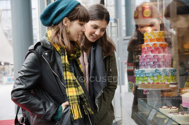 Women looking at cake shop window — Stock Photo