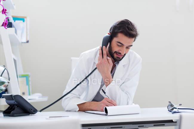 Врач за столом делает телефонный звонок — стоковое фото