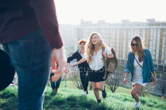 Group of friends running up hill — Stock Photo