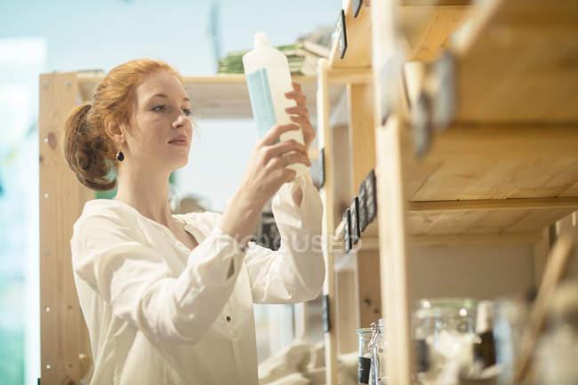 Женщина, собирание продукт от шельфа — стоковое фото