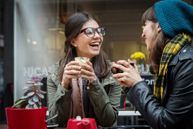 Young women at sidewalk cafe — Stock Photo