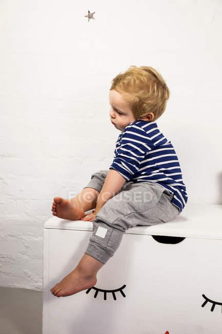 Мужской ребенок сидит — стоковое фото