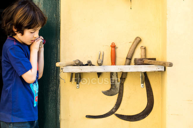 Young boy, looking at garden tools — Stock Photo