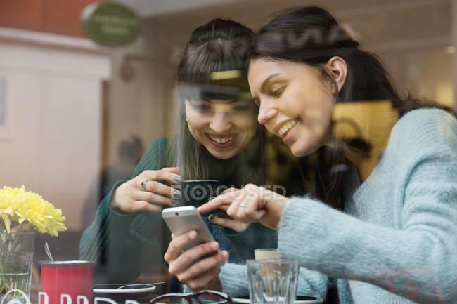 Due giovani donne che guardano smartphone — Foto stock