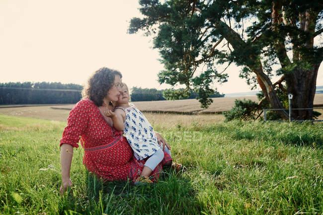 Женщина, сидящая в поле с дочерью — стоковое фото