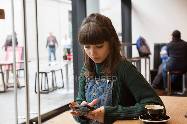 Молода жінка користується смартфоном. — стокове фото