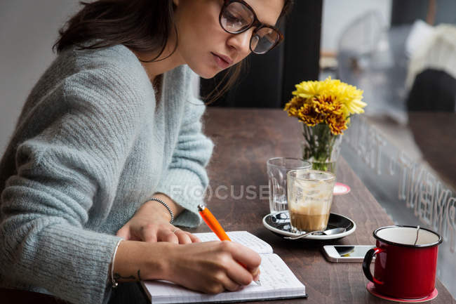 Young woman at cafe window seat writing notes — Stock Photo