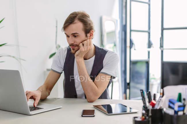 Man at desk using laptop — Stock Photo
