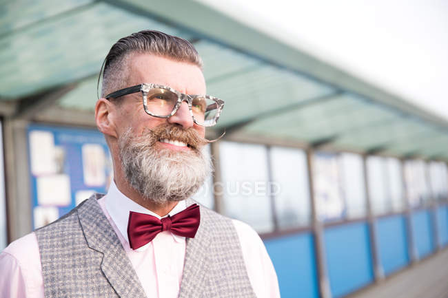 Man with eyeglasses and handlebar moustache on pier — Stock Photo