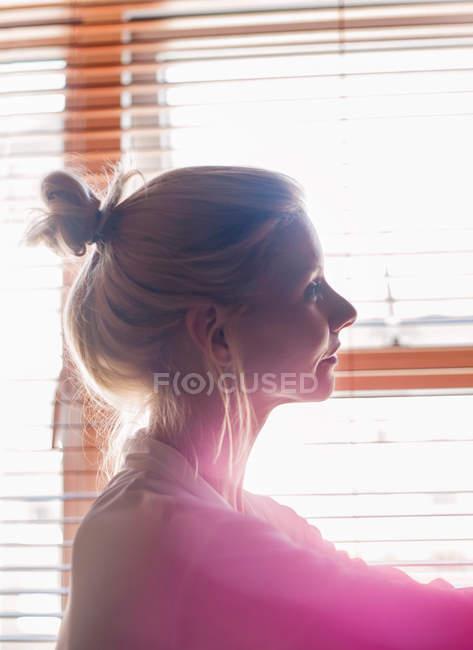 Молодая женщина у окна — стоковое фото
