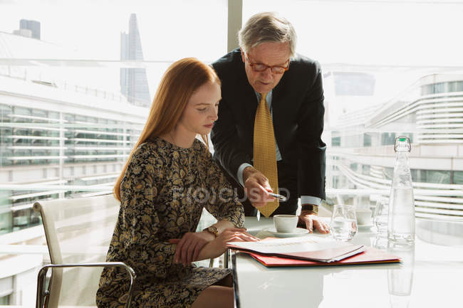 Businessman and businesswoman reading and analysing report — Stock Photo