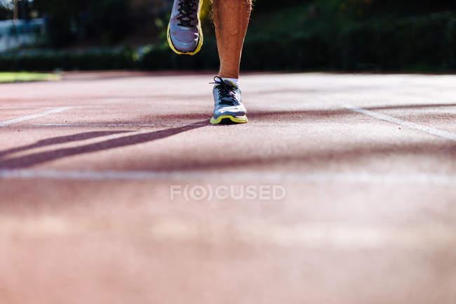 Feet of senior man running on racetrack — Stock Photo