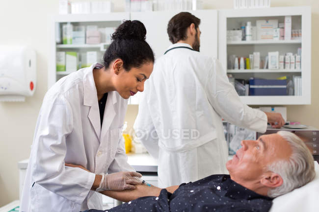 Doctor extracting patients blood — Stock Photo