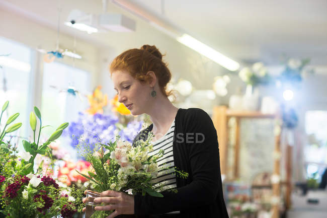 Florist selecting flowers in shop — Stock Photo
