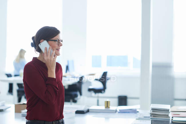 Woman in office making telephone call — Stock Photo