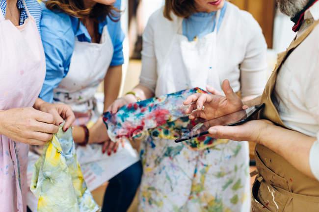 Menschen halten lackiert Stoff — Stockfoto