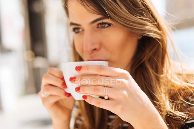 Молода жінка насолоджуючись кава — стокове фото