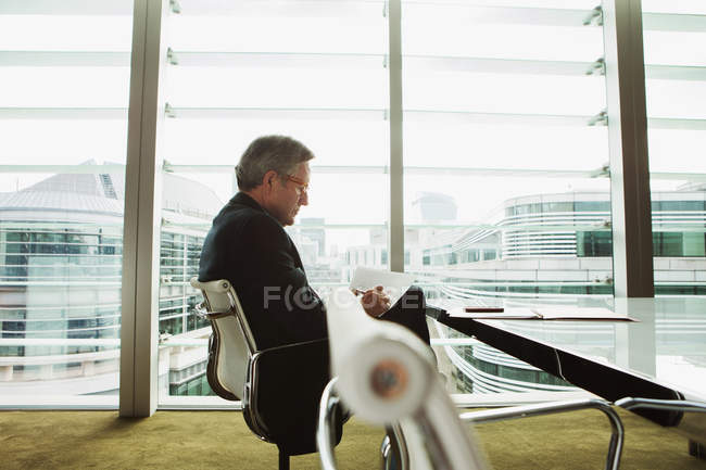 Businessman reading and analysing report — Stock Photo