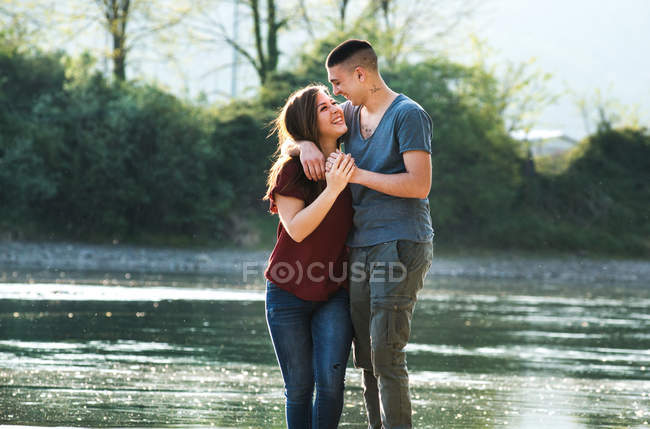Romantic couple standing beside river — Stock Photo