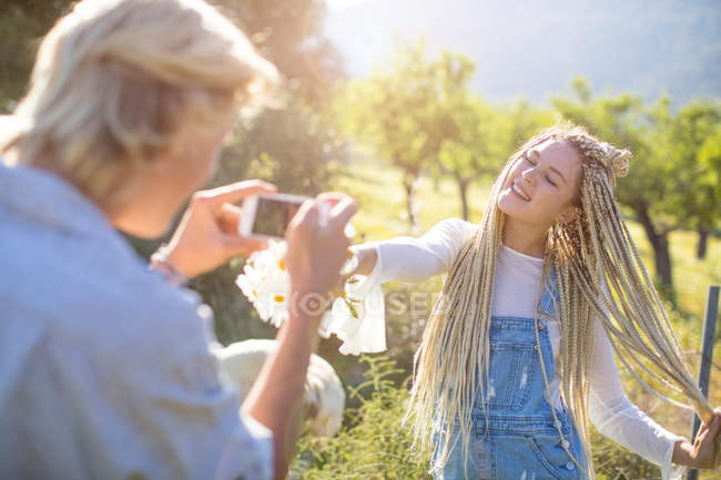 Man photographing girlfriend in field with wildflowers — Stock Photo