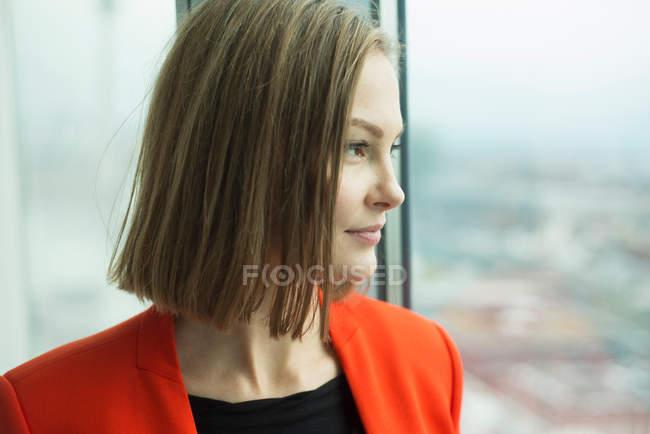 Бізнес-леді дивлячись через вікна офісу — стокове фото