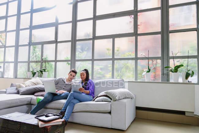 Pareja con portátil sentado en el sofá - foto de stock