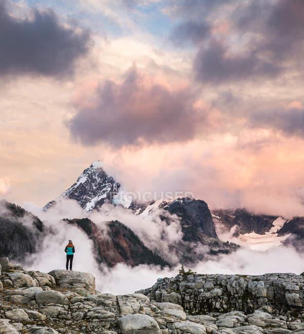 Турист, дивлячись на хмари на снігу покриті гори — стокове фото