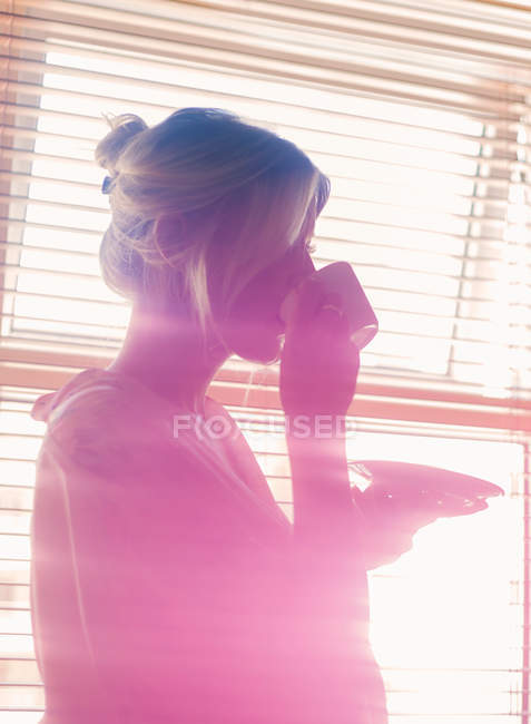 Woman drinking coffee beside window — Stock Photo