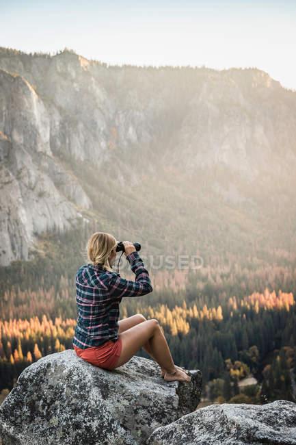 Mulher olhando através de binóculos — Fotografia de Stock