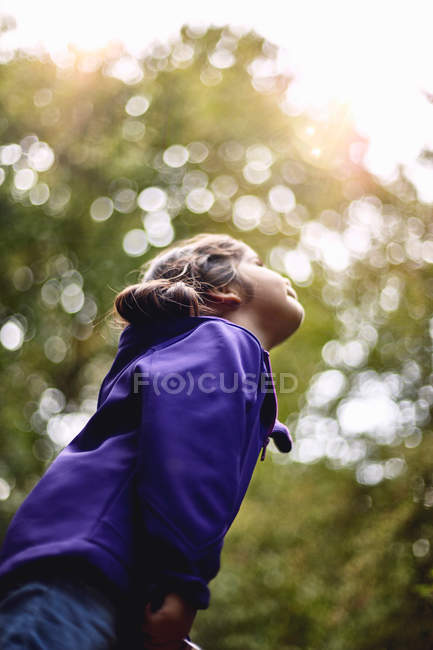 Young girl walking through forest — Stock Photo