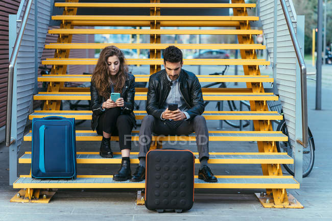 Couple using mobile phone on steps — Stock Photo