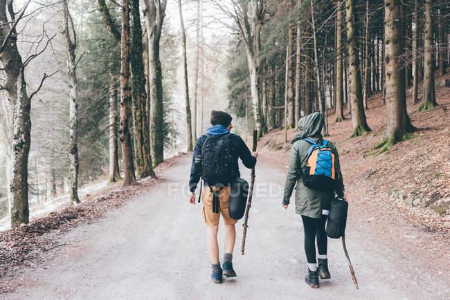 Escursionismo coppia escursioni lungo la strada forestale — Foto stock