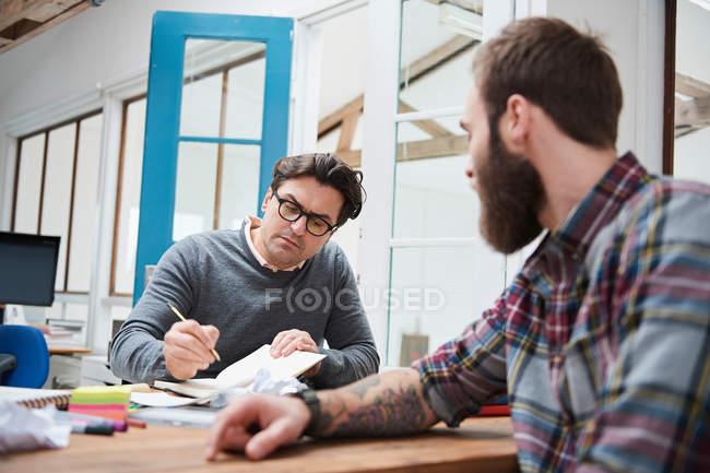 Мужчины-дизайнеры делают заметки — стоковое фото