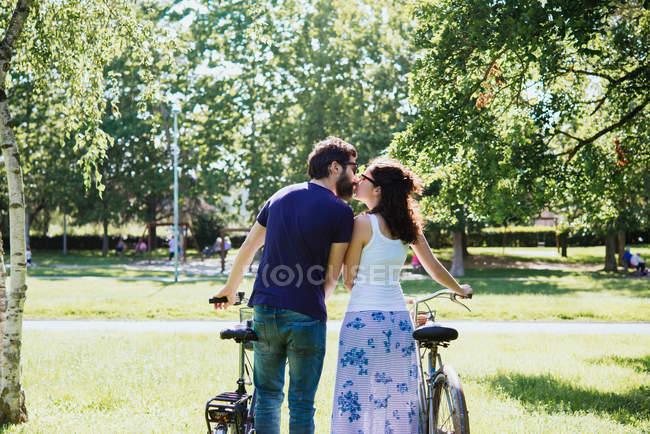 Casal com bicicletas beijando no parque — Fotografia de Stock
