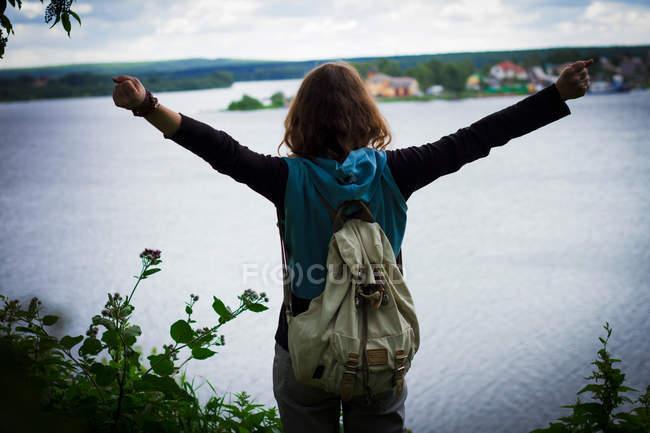 Mujer con los brazos levantados mirando hacia otro lado - foto de stock