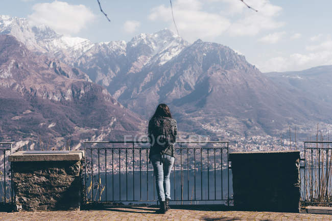Woman looking out over lake and mountains — Stock Photo