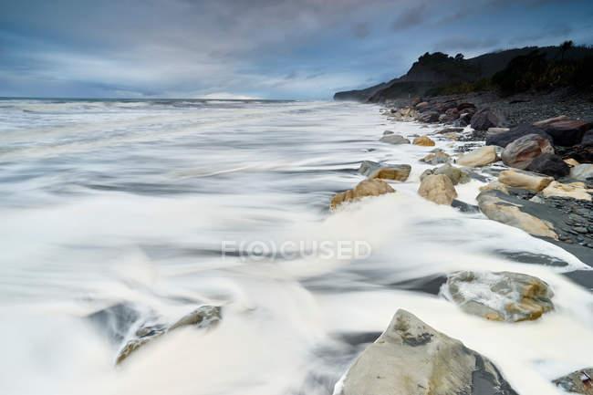 Onde sulla riva e cielo blu — Foto stock