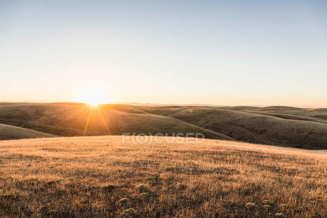 Sunset landscape view of rolling prairie hills — Stock Photo