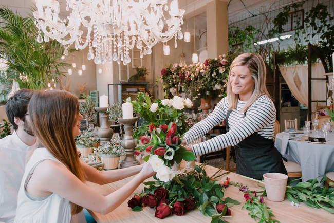 Florist handing flowers to customers — Stock Photo