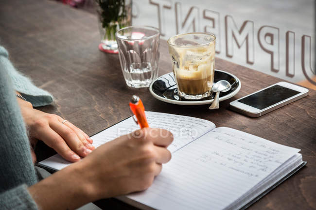 Woman at cafe window writing notes — Stock Photo
