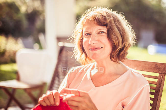 Senior femme, assise dans le jardin — Photo de stock