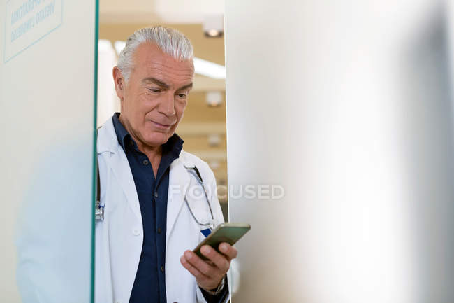 Doctor looking at mobile phone — Stock Photo