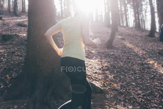 Female runner running in steep forest — Stock Photo